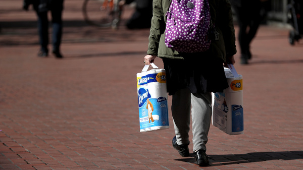 A pedestrian carries two packages of toilet paper as she walks along Market Street in San Francisco earlier this month.