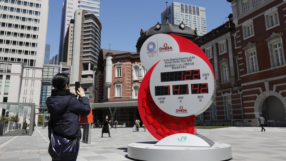 A person in Tokyo takes a photo of a clock counting down the days until the planned start of the Tokyo Games. They will now take place next year. (Yukihito Taguchi/USA Today Sports via Reuters)