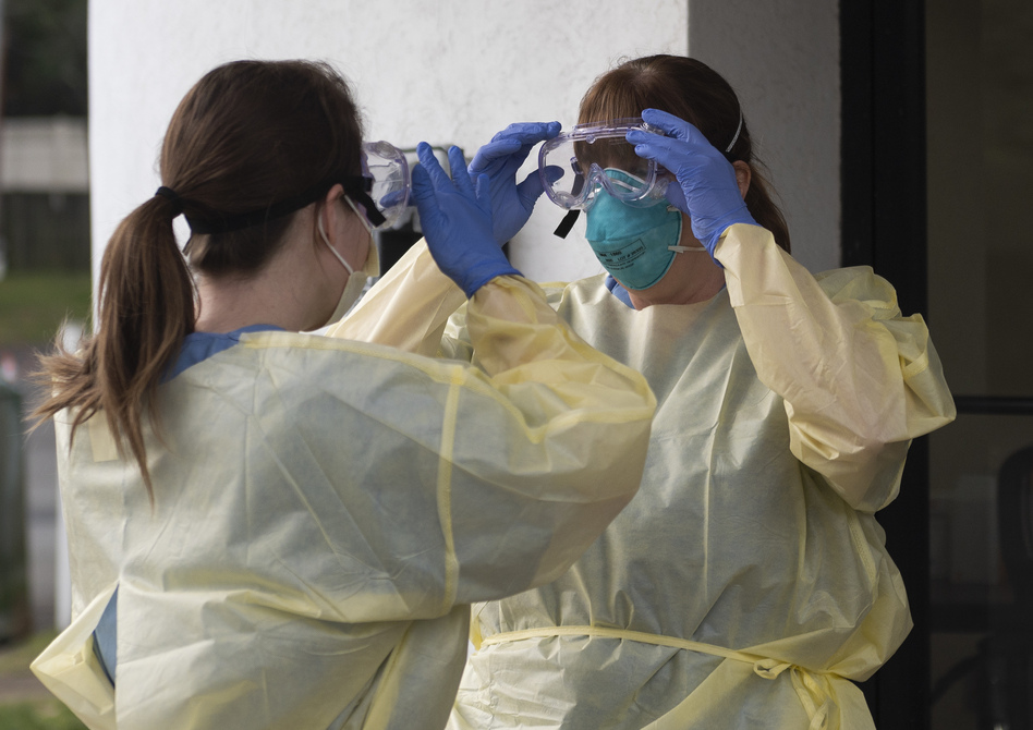 Health care workers from Virginia Hospital Center put on their personal protective equipment before people arrive at a drive-through coronavirus testing site in Arlington, Va., on Friday. (Andrew Caballero-Reynolds/AFP via Getty Images)