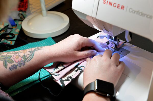 Stephanie Cave sews a mask last week in Dorchester, Mass.