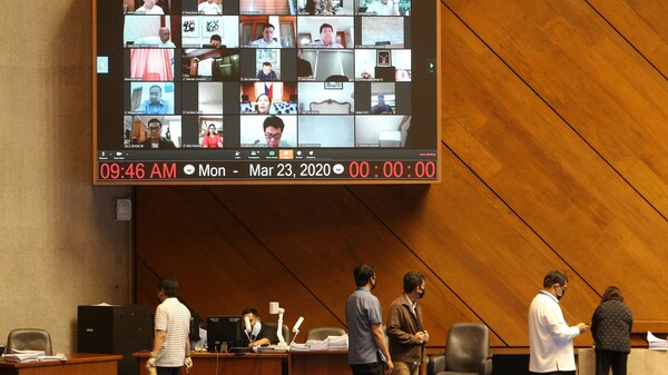 A huge video screen shows members of the Philippine Congress participating in a special session via video conference in Manila on Monday to discuss a proposed emergency power to be given to President Rodrigo Duterte to tackle the COVID-19 coronavirus outbreak.