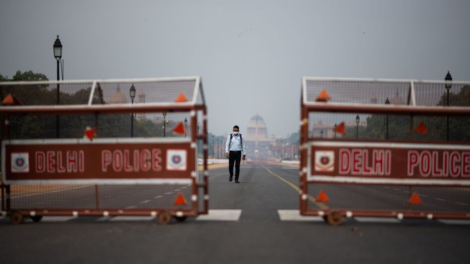 A man walks a deserted road in New Delhi. Indian Prime Minister Narendra Modi asked Tuesday that residents across the country stay where they are in order to help stem the spread of the coronavirus and the deadly disease it can cause, COVID-19. (Jewel Samad/AFP via Getty Images)
