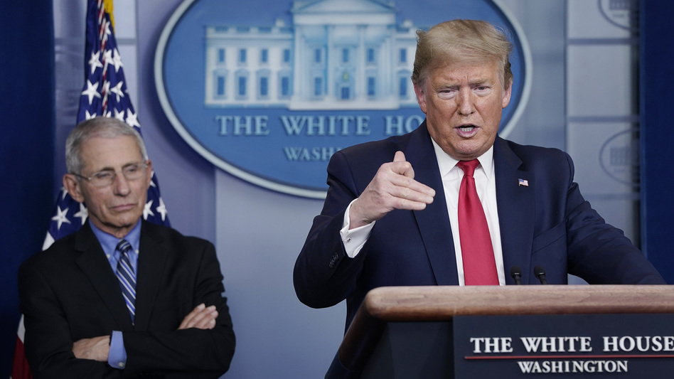 President Trump speaks while Dr. Anthony Fauci listens during Tuesday's briefing on the coronavirus pandemic. (Drew Angerer/Getty Images)