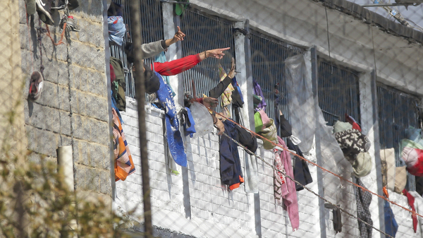 Inmates point from inside the La Modelo facility in Bogotá, Colombia, on Sunday. Violence broke out in the prison out of inmates