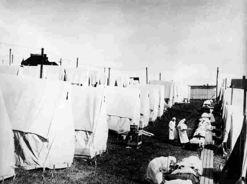 Masked doctors and nurses treat flu patients lying on cots and in tents at a hospital camp during the influenza pandemic of 1918.