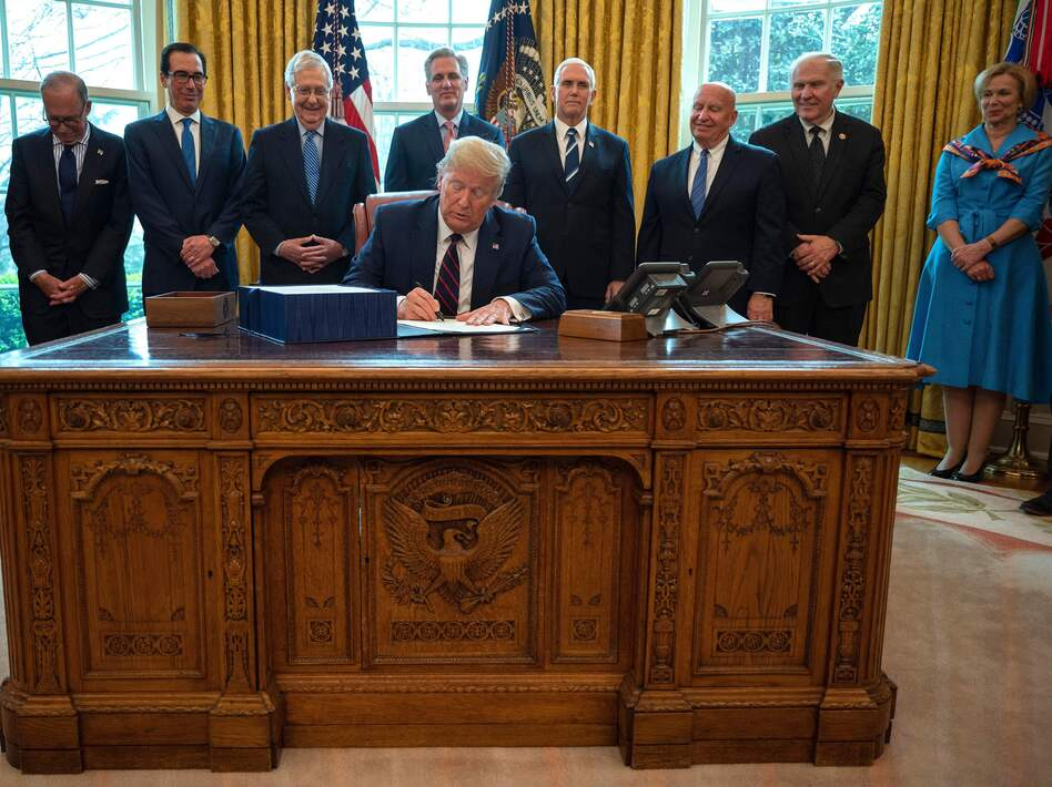 President Trump signs the CARES act, a $2 trillion rescue package to provide economic relief amid the coronavirus outbreak, at the Oval Office of the White House on Friday. (Jim Watson/AFP via Getty Images)