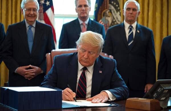 President Trump signs the CARES Act, a $2 trillion rescue package to provide economic relief amid the coronavirus outbreak, at the Oval Office on Friday.