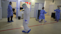 A health worker wears a protective suit at a nursing home, in Madrid, Spain, on Tuesday. With some of the highest cases of COVID-19 in the world, Spain's public health system is overstretched and in need of supplies.