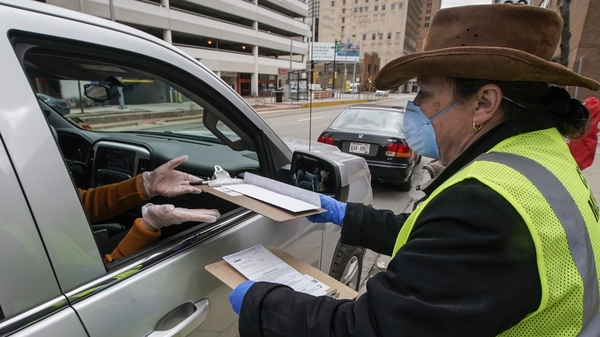 Jill Mickelson helps a drive up voter outside the Frank P. Zeidler Municipal Building Monday March 30, 2020, in Milwaukee. The city is now allowing drive up early voting for the state