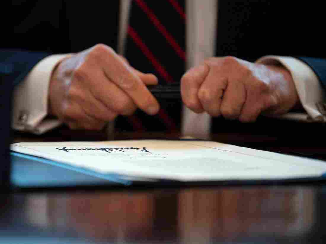 US President Donald Trump signs the CARES act, a $2 trillion rescue package to provide economic relief amid the coronavirus outbreak, at the Oval Office of the White House on March 27, 2020.  (Photo by JIM WATSON/AFP via Getty Images)