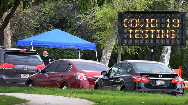 A police officer mans the entrance to a coronavirus testing center in Pacoima, Calif.