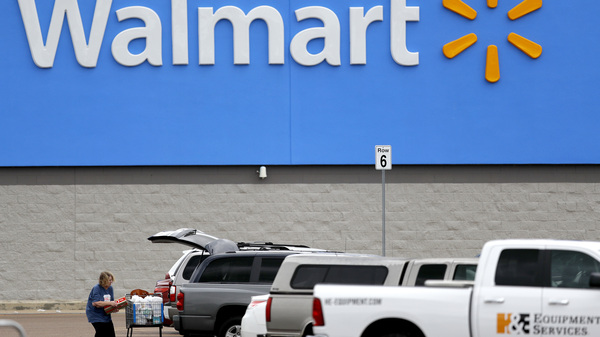 A woman loads groceries into her vehicle outside of a Walmart store in Pearl, Miss., on March 31.