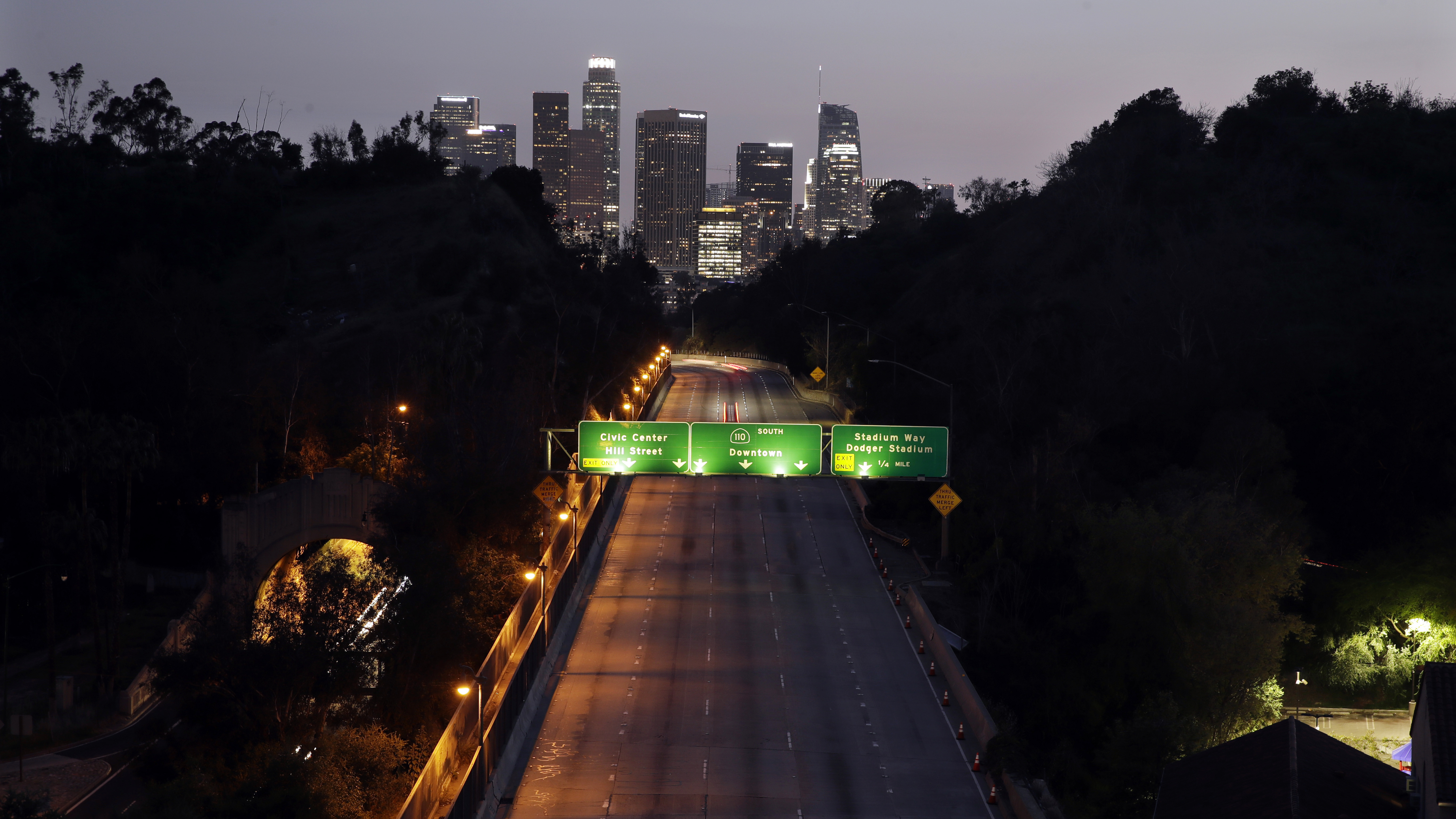 California State Route 110 seen with downtown Los Angeles in the background Thursday night. The state is in its second week of a lockdown, where schools and nonessential businesses are closed and the governor has ordered people to stay home.