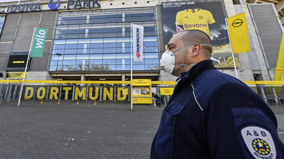 Security with face masks stand in front of the Signal Iduna Park, where a temporary coronavirus treatment center opened in Dortmund, Germany, Saturday. Germany has the fourth-most COVID-19 cases in the world and demand for medical supplies has skyrocketed. (Martin Meissner/AP)