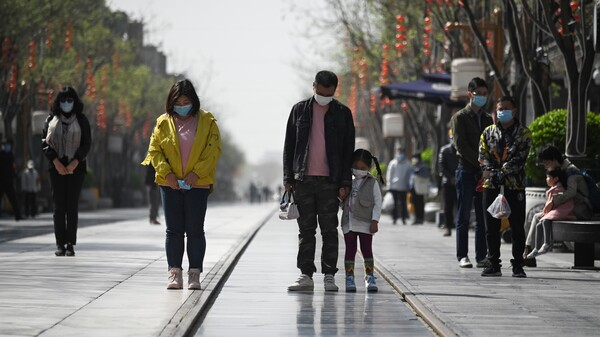 People in face masks observe three minutes of silence in Beijing, on a national day of mourning for the thousands of patients and medical workers killed by the coronavirus in China.