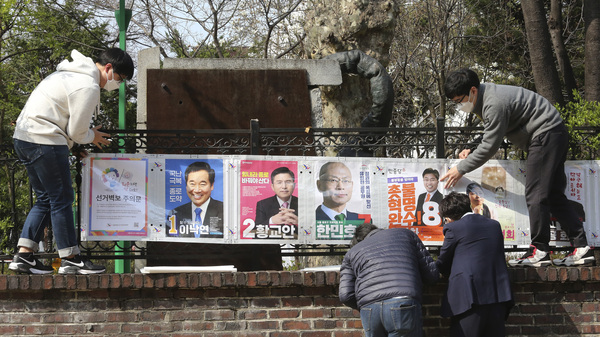 South Korean election officials put posters of candidates in Seoul, South Korea, on April 2. The country will hold April 15 legislative elections on schedule, and the government