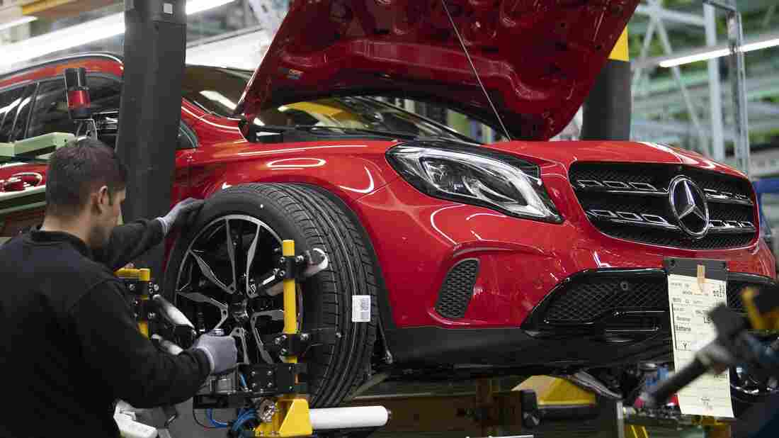 An employee mounts a wheel on a Mercedes-Benz A Class on the assembly line at the Daimler AG factory in Rastatt, southwestern Germany.