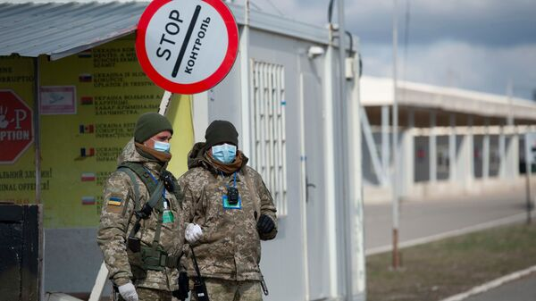 Ukrainian border guards wear protective face masks at a checkpoint with the territories controlled by Russia-backed separatists in the Donetsk region.