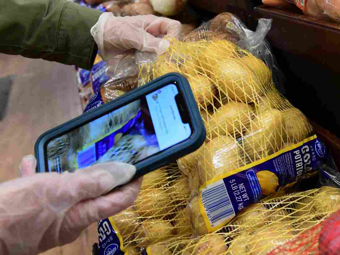 Instacart employee Monica Ortega uses her cellphone to scan barcodes showing proof of purchase for the customer while picking up groceries (Photo by FREDERIC J. BROWN/AFP via Getty Images)
