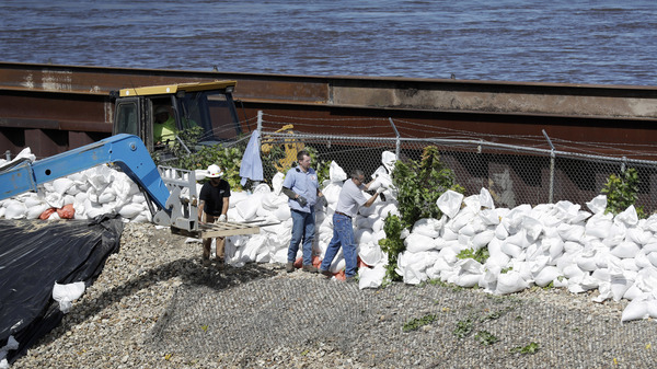 Workers build a sandbag wall near the Cedar River in Iowa in 2016. Disaster response experts say aid workers and others who could assist may not be able to travel during the pandemic.
