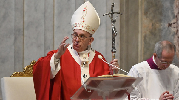 """Pope Francis hailed """"the saints who live next door"""" during the COVID-19 pandemic, saying doctors and others who are still working are heroes. The pope is seen here celebrating Palm Sunday Mass behind closed doors because of the coronavirus."""