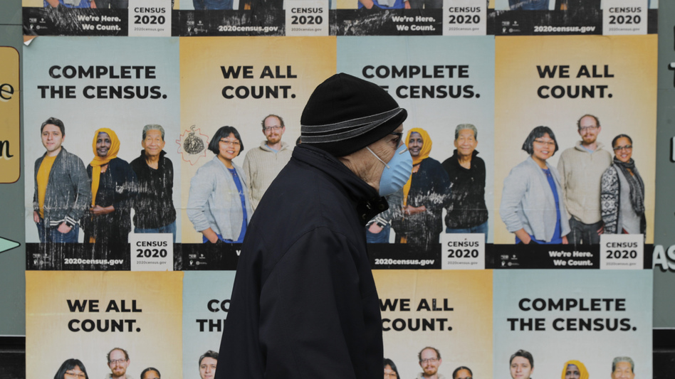 A person wearing a mask walks past posters encouraging participation in the 2020 census in April in Seattle. (Ted S. Warren/AP)