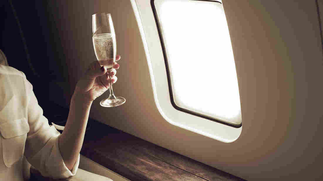 A woman on a private plane holds champagne.