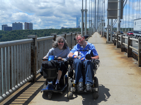 Dr. Lisa Iezzoni and her friend, Michael Ogg, crossing the George Washington Bridge, over New York's Hudson River, in their motorized wheelchairs, after Ogg survived a cancer diagnosis. Iezzoni has written about another doctor who declined to do a physical exam of Ogg. Merely lifting his shirt would have revealed evidence of cancer, she says.
