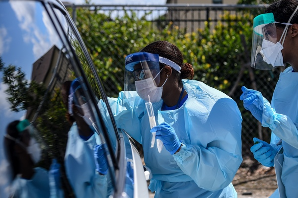 Medical personnel take patient samples at a drive-through coronavirus testing site in West Palm Beach, Florida, Monday, March 16, 2020.