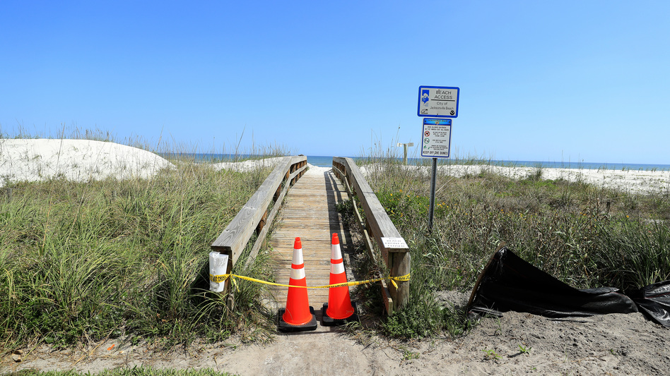 "Police tape and pylons block the public access to Jacksonville Beach last month amid the coronavirus outbreak. The mayor of Jacksonville, Fla., says parks and beaches in Duval County would reopen Friday for ""essential activities"" only. (Sam Greenwood/Getty Images)"