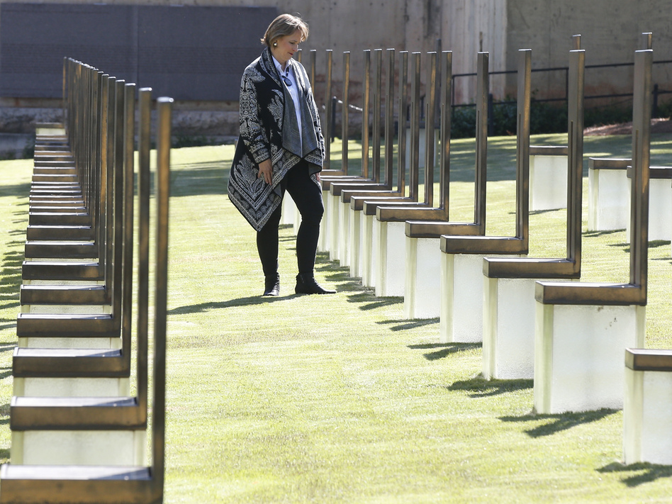 Lynne Gist stands at her sister's chair in the Field of Empty Chairs at the Oklahoma City National Memorial and Museum on Wednesday. Gist lost her sister, Karen Gist Carr, when a truck bomb ripped through a federal building in downtown Oklahoma City and killed 168 people 25 years ago. (Sue Ogrocki/AP)