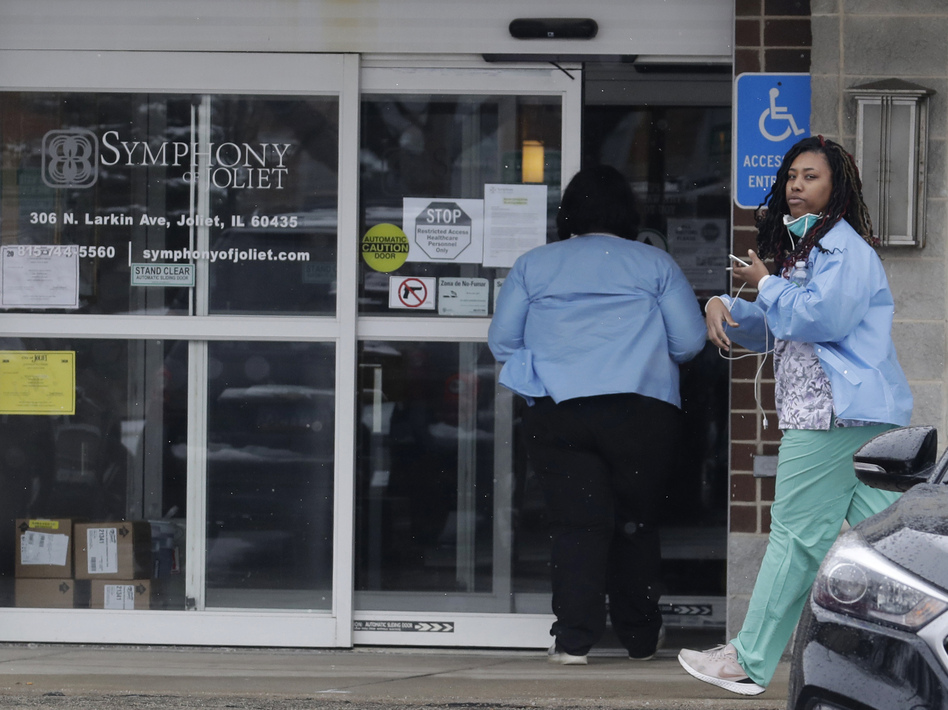 Employees of the Symphony of Joliet nursing home in Joliet, Ill., go to work last Friday. At least 21 people, including two staff members, have died of COVID-19 at the facility. (Nam Y. Huh/AP)