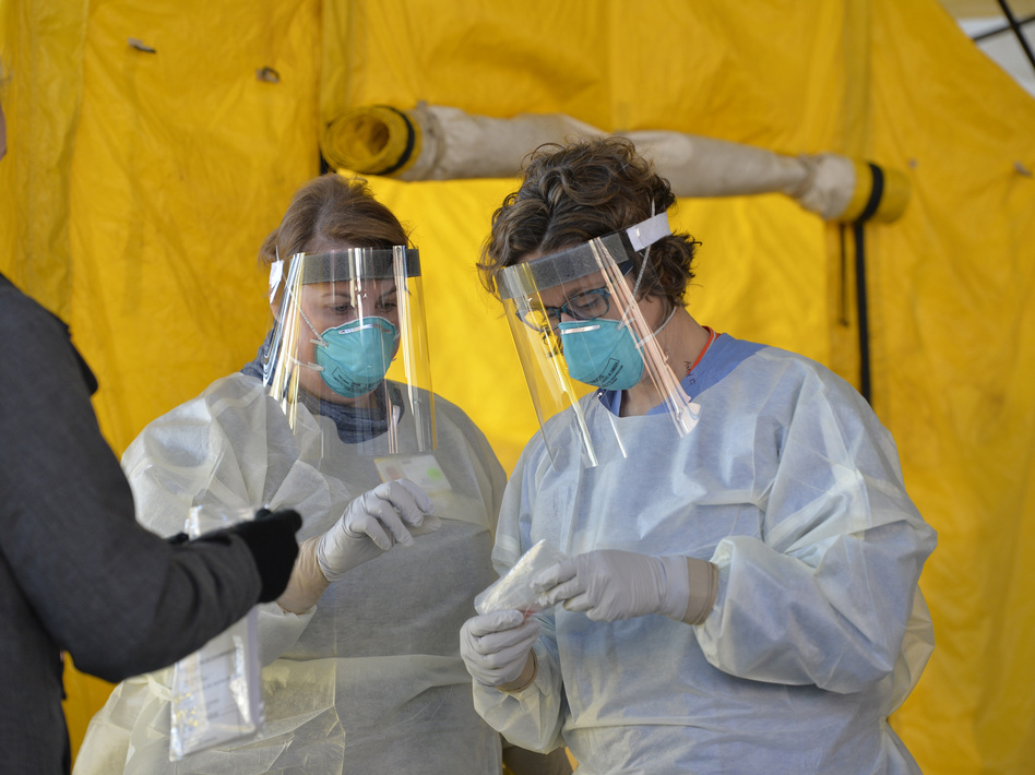 Hospital clinicians in Newton, Mass., work with test kits to determine if patients have the coronavirus. New York Gov. Andrew Cuomo says President Trump agreed Tuesday to help his state get more of the  supplies needed to expand testing. (Joseph Prezioso/AFP via Getty Images)