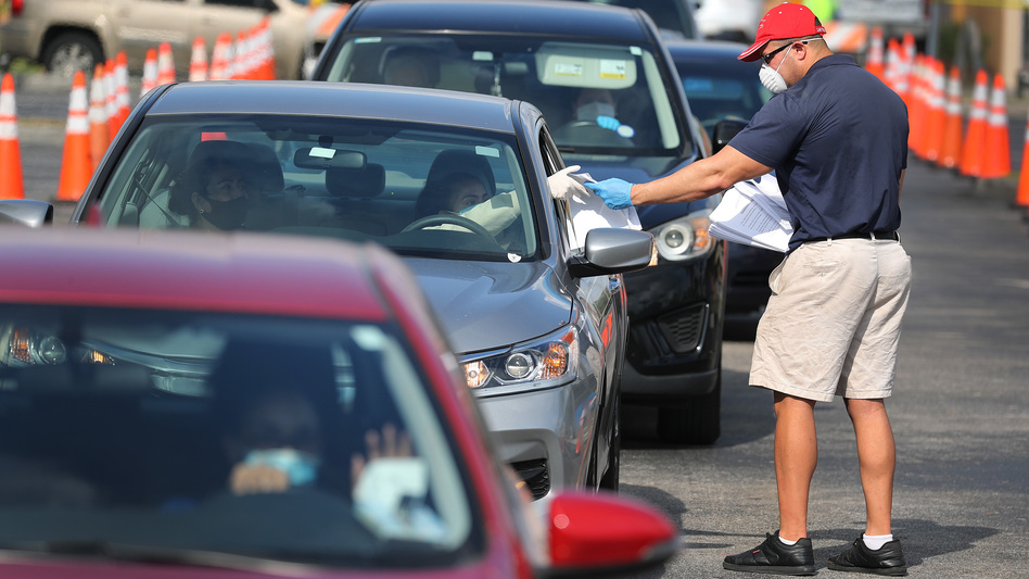 Miguel Diaz hands out unemployment applications to people in their vehicles on April 8 in Hialeah, Fla. Black, Latino and Asian American workers have lost jobs at a faster clip than white employees during the coronavirus pandemic. (Joe Raedle/Getty Images)