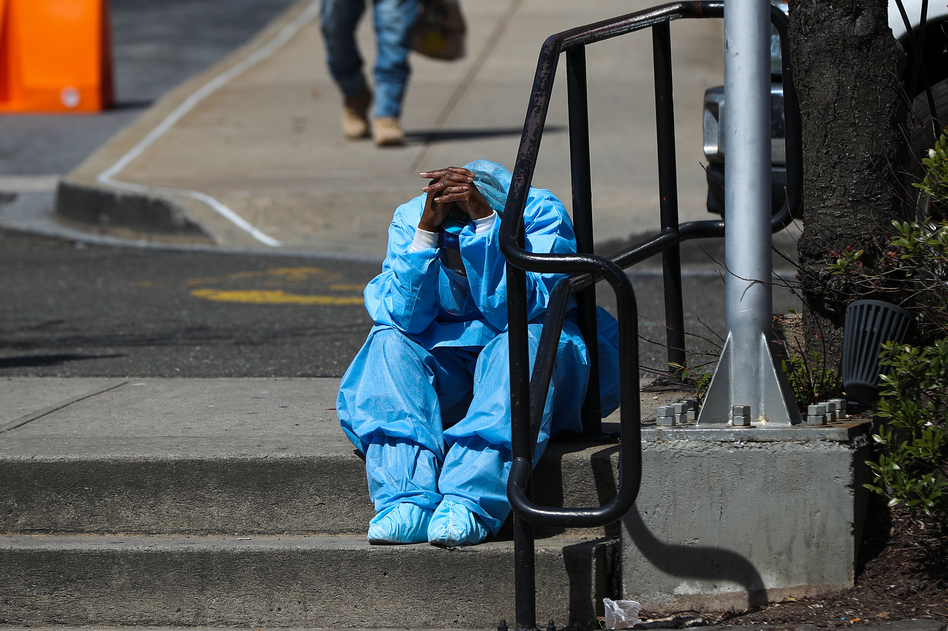 A fatigued health care worker takes a moment outside the Brooklyn Hospital Center in April. Many hospital workers these days have to cope with horrific tragedies playing out multiple times on a single, 12-hour shift. (Tayfun Coskun/Anadolu Agency via Getty Images)
