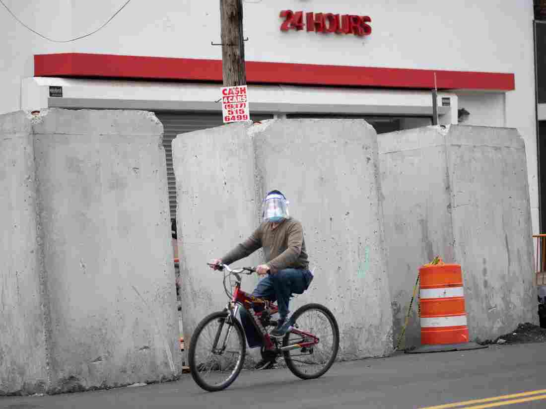 A man wearing a mask pedals his bike in the Corona neighborhood of Queens on April 14, 2020 in New York City. - New York will start making tens of thousands of coronavirus test kits a week, its mayor announced Tuesday, as the city looks to boost testing capacity with a view to ending its shutdown. (Photo by Johannes EISELE / AFP) (Photo by JOHANNES EISELE/AFP via Getty Images)
