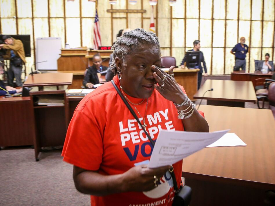 Carmen Brown weeps as she walks away holding a paper restoring her right to vote during a special court hearing aimed at restoring that right in a Miami-Dade County courtroom on Nov. 8, 2019. A federal lawsuit currently underway would make it easier for others to get their voting rights restored by eliminating requirements that they pay fines and fees. (Zak Bennett/AFP via Getty Images)