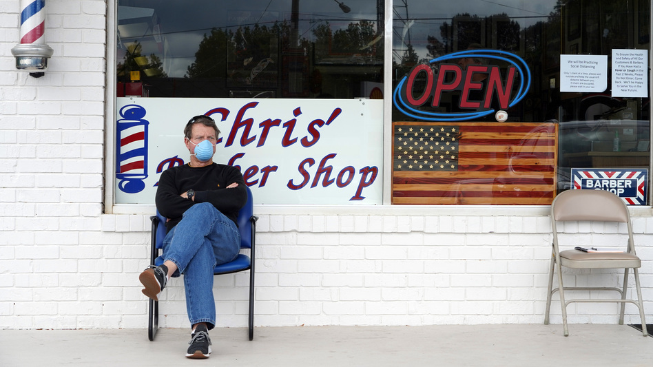Dan Settle sits outside Chris' Barber Shop as he waits his turn for a haircut in Lilburn, Ga., on Friday. (Tami Chappell/AFP via Getty Images)