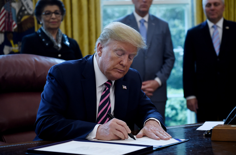 President Trump a new coronavirus economic aid package, largely targeted to support small businesses, in the Oval Office on Friday. (Olivier Douliery/AFP via Getty Images)
