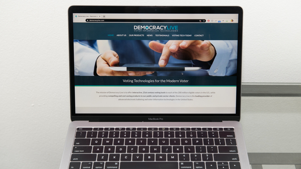 The Democracy Live home page is displayed on an Apple laptop computer. The company is administering a ballot return system for disabled voters in West Virginia, Delaware, and potentially New Jersey.