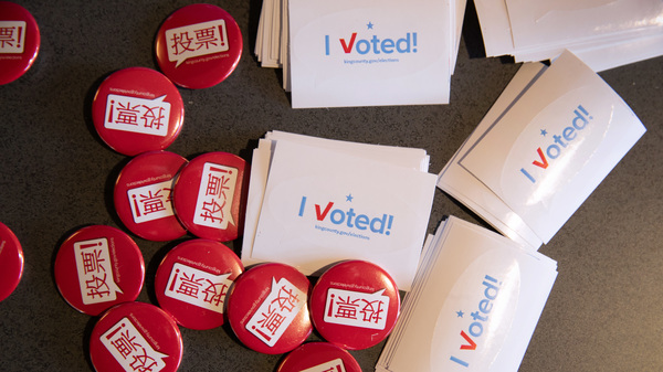 Voting pins and stickers lie next to a ballot box earlier this year during early voting at the King County Elections processing center in Washington.