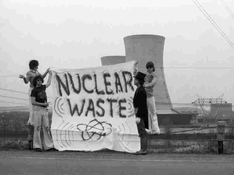 With one man dressed as an undertaker, a group of people unfurl a protest banner in front of the cooling towers at the Three Mile Island nuclear power plant.