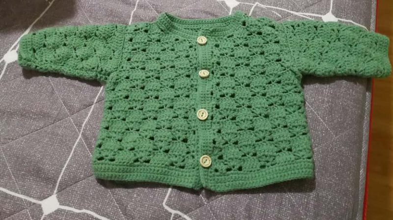 A green sweater that Jessie crocheted in China while waiting for Jacquie, her American surrogate, to deliver her baby.