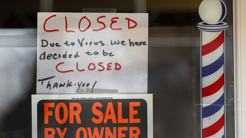 Signs are displayed in the window of a store in Grosse Pointe Woods, Mich. The Paycheck Protection Program, aimed at helping small businesses survive the coronavirus crisis, has been beset by problems. (Paul Sancya/AP)