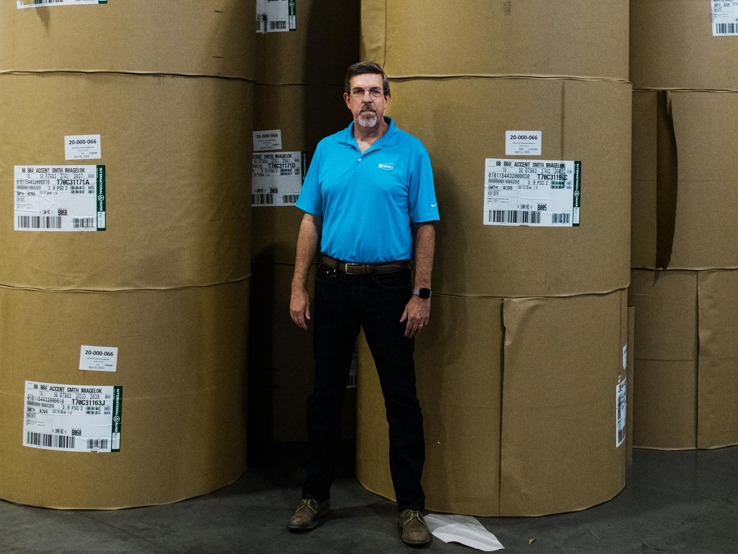 Jeff Ellington, président et chef de l'exploitation de Runbeck Election Services, se tient devant d'énormes rouleaux de papier utilisés pour créer des bulletins de vote postal.