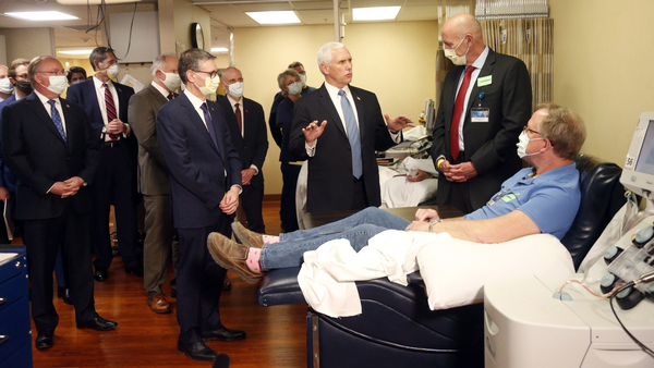 Vice President Pence visits with coronavirus survivor Dennis Nelson at the Mayo Clinic in Rochester, Minn., during a tour of facilities supporting COVID-19 research and treatment Tuesday.