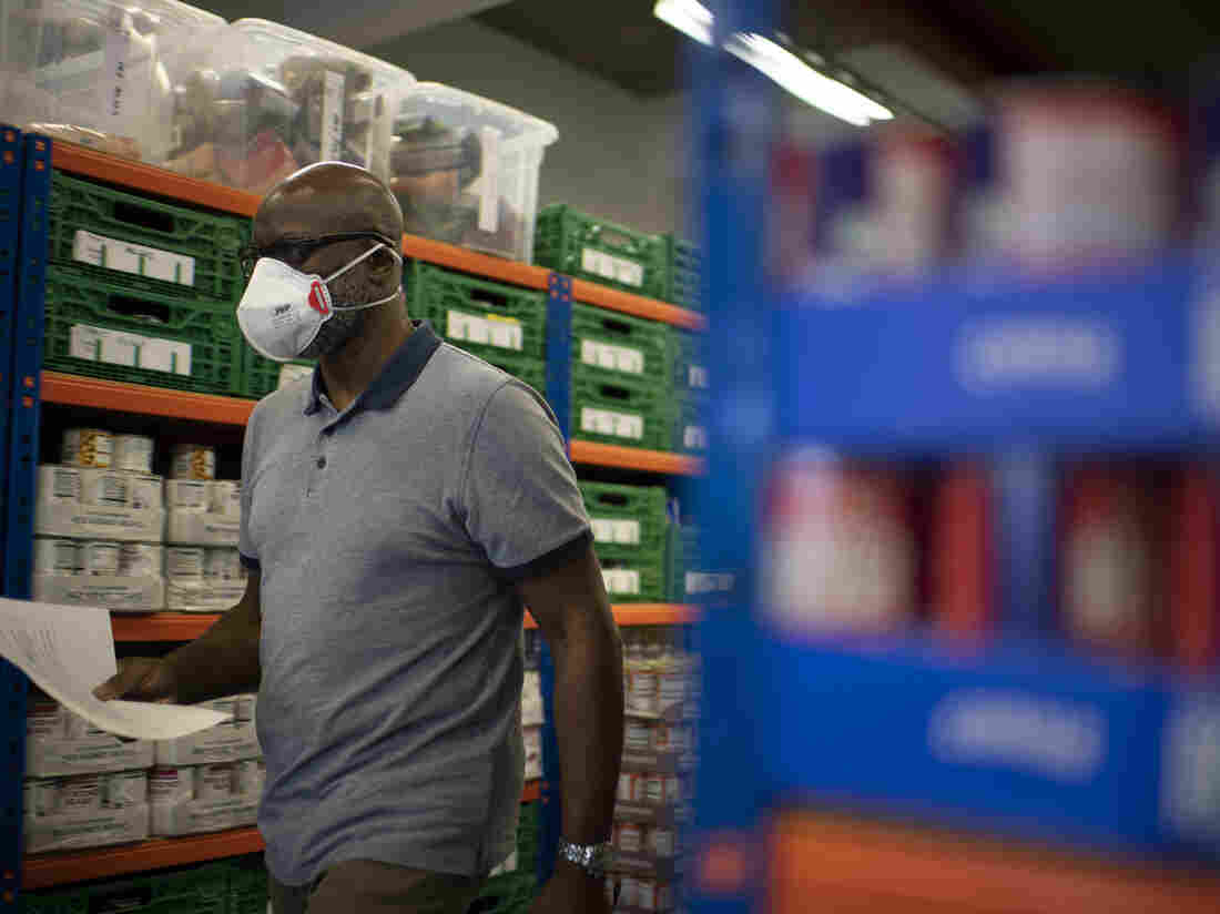 Co-founder and Chair of the First Love foundation foodbank, Aerold Bentley walks past goods for distribution to families, at the First Love foundation foodbank warehouse in Tower Hamlets in east London on April 24, 2020, (Photo by DANIEL LEAL-OLIVAS/AFP via Getty Images)