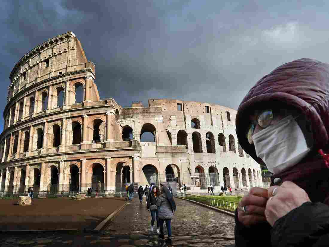 TOPSHOT - A man wearing a protective mask passes by the Coliseum in Rome on March 7, 2020 amid fear of Covid-19 epidemic. - Italy on March 6, 2020 reported 49 more deaths from the new coronavirus, the highest single-day toll to date, bringing the total number of fatalities over the past two weeks to 197. (Photo by Alberto PIZZOLI / AFP) (Photo by ALBERTO PIZZOLI/AFP via Getty Images)