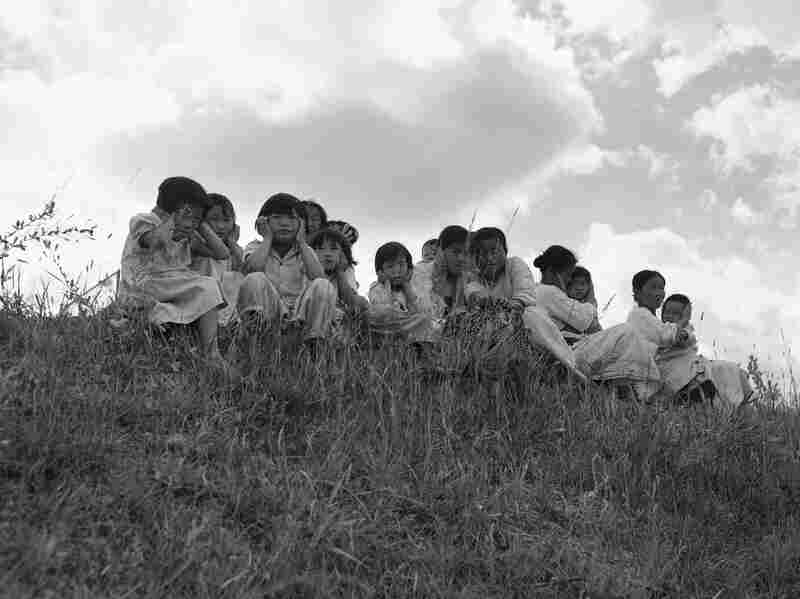 South Korean mothers and children shield themselves as they watch U.S. 105mm howitzers blast enemy positions across the Han River. The attack occurred during the U.S. drive from Gimpo to Seoul on Sept. 24, 1950.