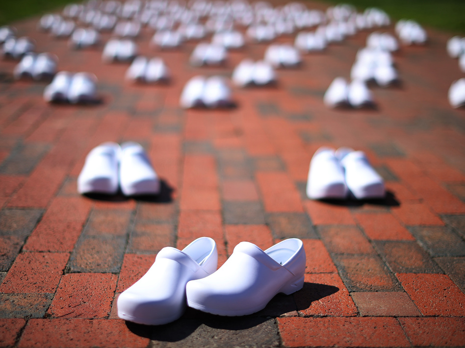As part of a demonstration across from the White House on May 7, National Nurses United set out empty shoes for nurses who have died from COVID-19. The union is asking employers and the government to provide safe workplaces, including adequate staffing. Hospitals have been laying off and furloughing nurses due to lost revenue. (Chip Somodevilla/Getty Images)